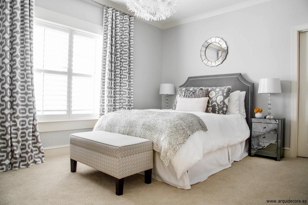Dormitorio decorado en tonos grises y blancos, con moqueta beige